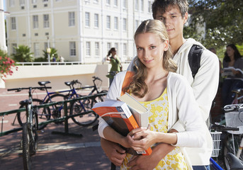 A young couple together standing by a bike rack