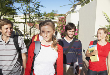 Five students walking on a campus