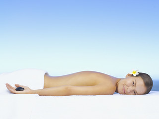 A woman lying on a massage table holding a massage stone