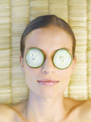 Woman relaxing with cucumber slices on her eyes