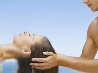 Woman getting a head massage from a masseur