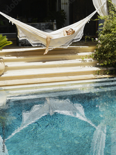 Woman relaxing in a hammock by a pool