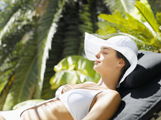 Woman sun tanning in a lounge chair