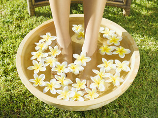 A woman's feet soaking in a bowl of water and flowers
