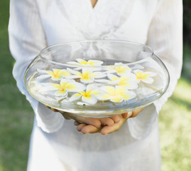 Woman holding a bowl of water and flowers