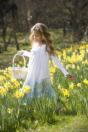 Girl Walking Through Daffodils with Basket Of Easter Eggs