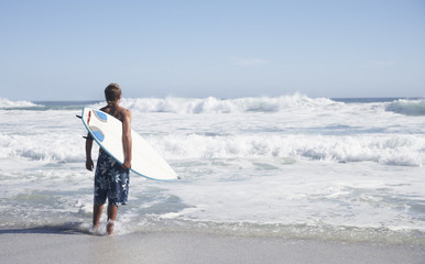 Man standing on the beach with his surfboard