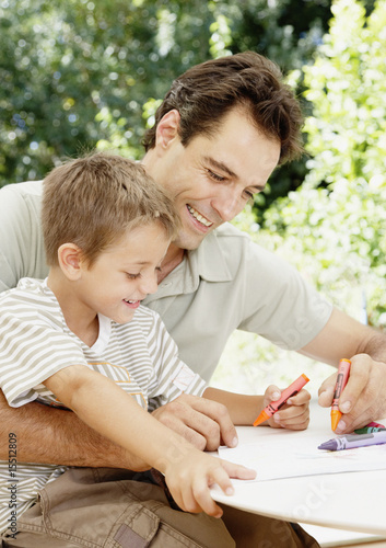 A father and son colouring together