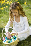 Young Girl Looking at Basket Full of Easter Eggs