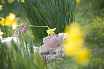 Young Woman Laying on Grass Holding Daffodil