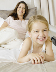 A mother and daughter relaxing on a bed