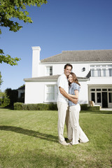 A couple embracing on the front lawn of a large home
