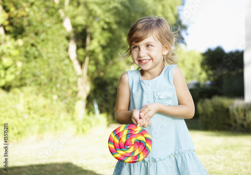 A young girl holding a large lollipop