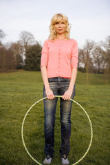 Young Woman Standing With Hula Hoop Smiling