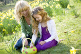Mother and Daughter Looking at Basket Of Easter Eggs