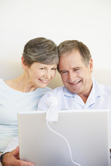 a mature couple using a laptop sitting in bed