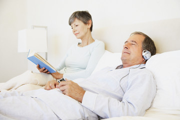a senior couple reading and listening to headphones in bed