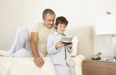 a grandfather watching his grandson play a handheld game