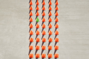 One green pylon amid forty-four orange pylons