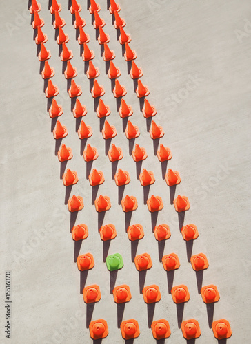 One green pylon amid seventy-four orange pylons