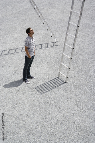 Man looking up at ladder outdoors