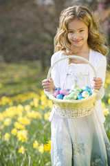 Young Girl Holding Basket Full of Easter Eggs Smiling