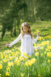 Girl walking through daffodils with a basket of Easter eggs