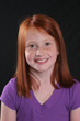 Smiling redhead girl on dark background