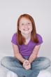 Smiling redhead girl sitting on floor