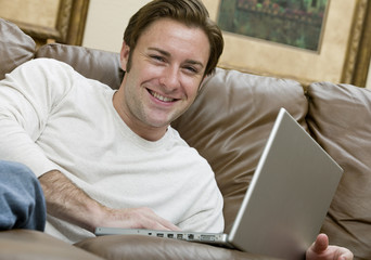An attractive man relaxing on the couch while on his computer