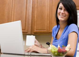 A young woman on her computer while having breakfast
