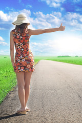 Back of woman hitchhiking the road