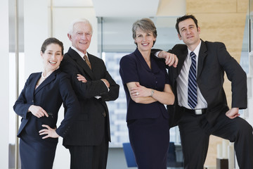 Three quarter length vew of four businesspeople smiling in hallw