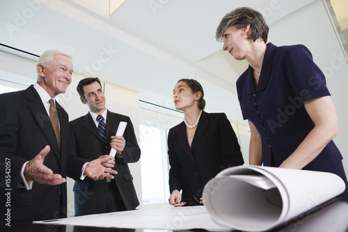 Four businesspeople standing over plans in a meeting.