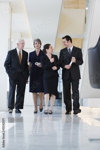 Front view of four executives walking in corridor deep in discus