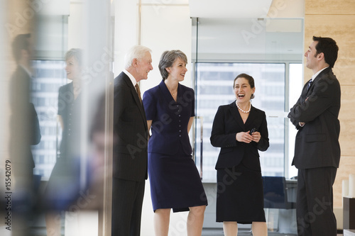View of businesspeople smiling and conversing in an office.