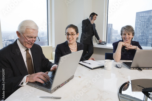 Four executives meeting with laptops in a conference room.