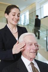 Businesswoman massaging senior executive's headache.