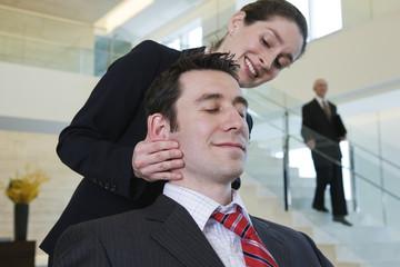 Businesswoman massaging stressed executive's head.