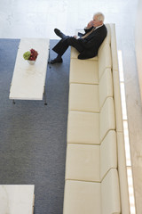 Elevated view of senior manager on cellphone in lobby.