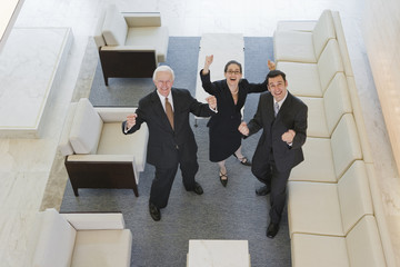 Successful colleagues gesturing in offce lobby.