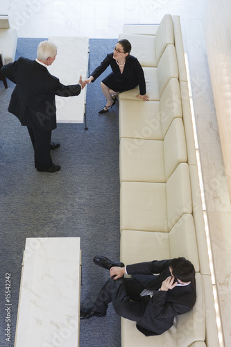 Elevated view of businesspeople shaking hands in a lobby.