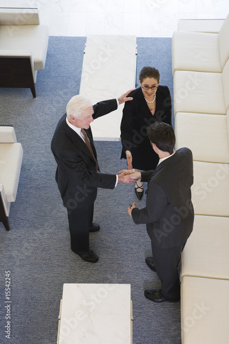 Elevated view of businesspeople shaking hands in an office lobby