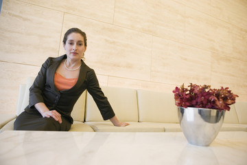 Portrait of businesswoman seated in lobby.