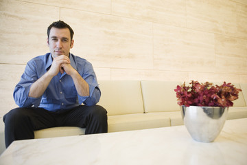 Portrait of businessman sitting and thinking in lobby.