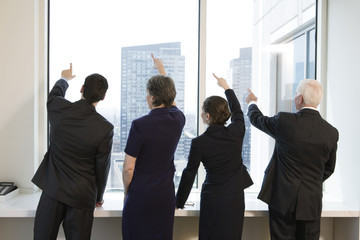 Four businesspeople at a window pointing up.