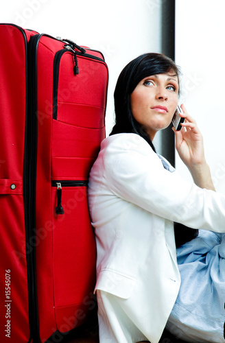 businesswoman sitting with luggage on airport phoning