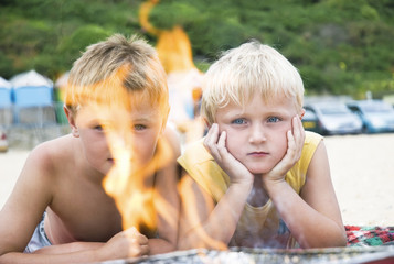 Two young brothers staring at barbecue flames.