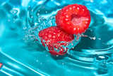 Fototapety Fresh raspberry on a background of blue water.