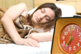 Young woman snoozing a red alarm clock poster